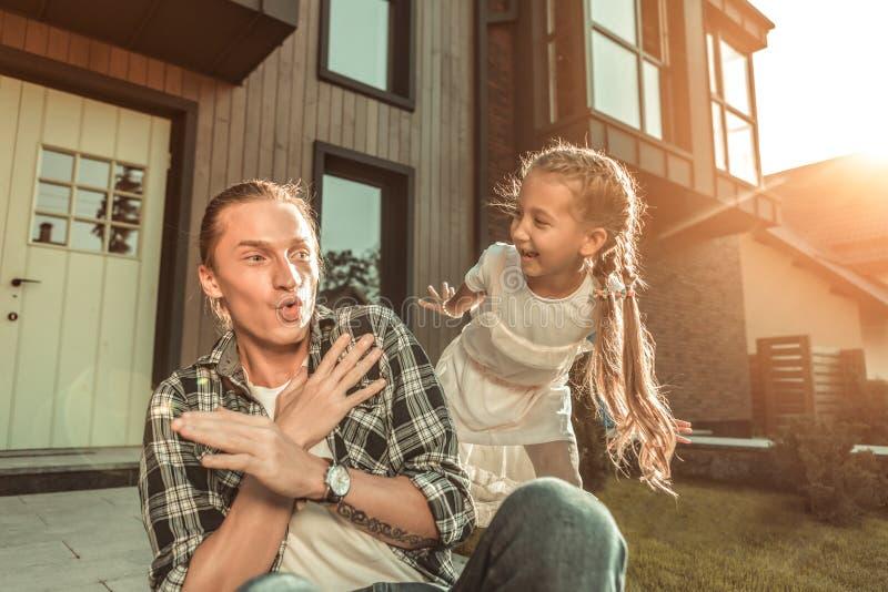 Ενεργός όμορφος πατέρας στο ελεγμένο πουκάμισο που έχει το χρόνο παιχνιδιών με την κόρη της στοκ φωτογραφία με δικαίωμα ελεύθερης χρήσης