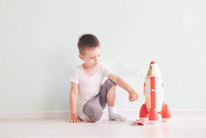 Ενεργό μικρό παιδί που παίζει τα παιχνίδια πυραύλων, παιδί που παρουσιάζουν παιχνίδι πυραύλων με την ευτυχή εκμάθηση προσώπου, πα στοκ εικόνες