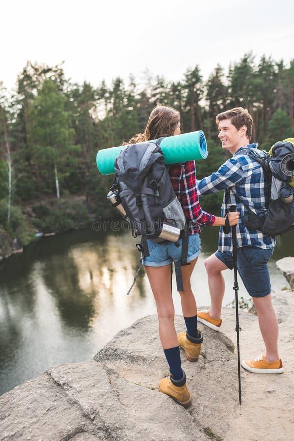 ενεργό νέο ζεύγος με τα σακίδια πλάτης που έχουν το ταξίδι πεζοπορίας και στάση στον απότομο βράχο στοκ φωτογραφίες με δικαίωμα ελεύθερης χρήσης