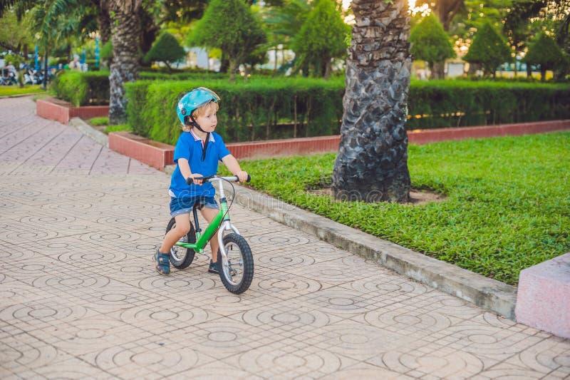 Ενεργό ξανθό οδηγώντας ποδήλατο αγοριών παιδιών στο πάρκο κοντά στη θάλασσα Παιδί μικρών παιδιών που ονειρεύεται και που έχει τη  στοκ φωτογραφία