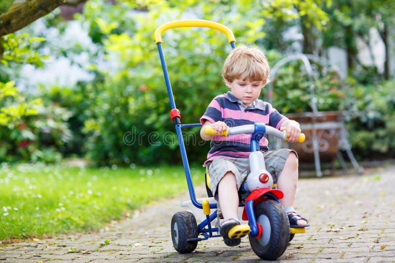 Ενεργό ξανθό τρίκυκλο ή ποδήλατο αγοριών παιδιών οδηγώντας εσωτερικό gar στοκ φωτογραφίες