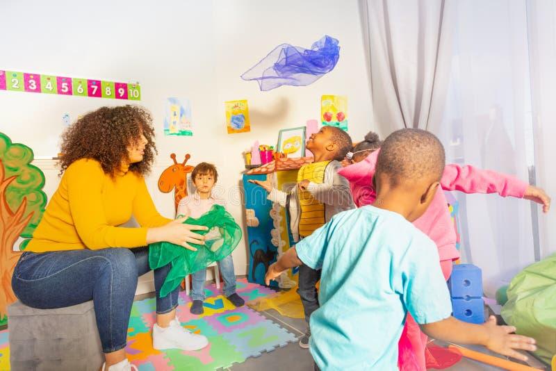 Ενεργό παιχνίδι διασκέδασης με τα παιδάκια που ρίχνουν το ύφασμα στοκ φωτογραφία με δικαίωμα ελεύθερης χρήσης