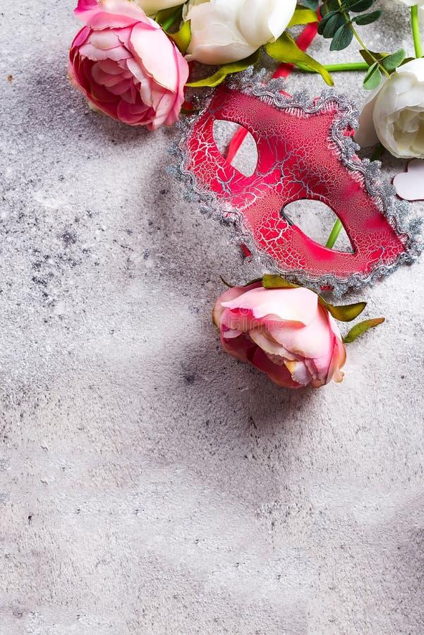 Ενετικά μάσκα και λουλούδια στο υπόβαθρο πετρών Έννοια ραντεβού στα τυφλά, διάστημα αντιγράφων στοκ εικόνες με δικαίωμα ελεύθερης χρήσης