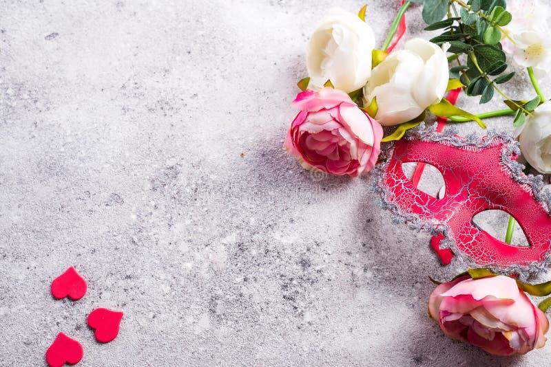Ενετικά μάσκα και λουλούδια στο υπόβαθρο πετρών Έννοια ραντεβού στα τυφλά, διάστημα αντιγράφων στοκ φωτογραφία με δικαίωμα ελεύθερης χρήσης