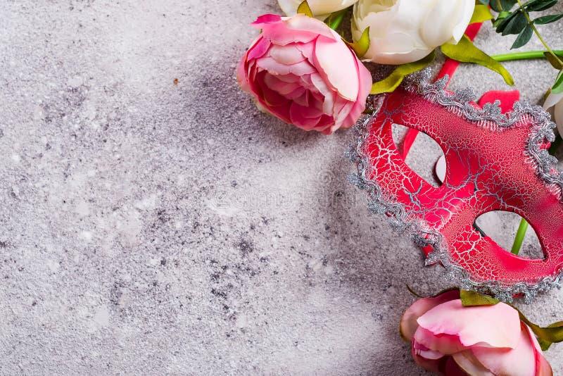 Ενετικά μάσκα και λουλούδια στο υπόβαθρο πετρών Έννοια ραντεβού στα τυφλά, διάστημα αντιγράφων στοκ εικόνες