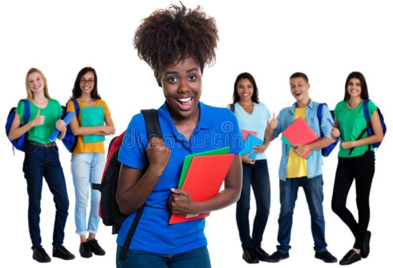 Ενθαρρυντική γυναίκα σπουδαστής αφροαμερικάνων με την ομάδα σπουδαστών στοκ φωτογραφίες