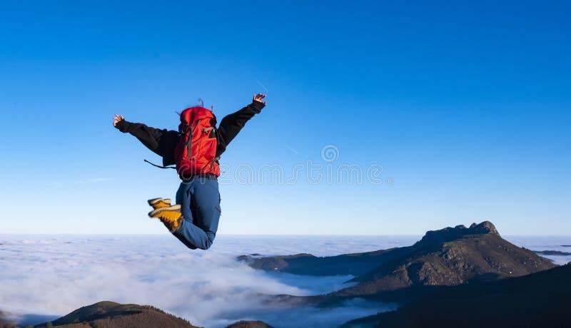 Ενθαρρυντική ευτυχής νέα γυναίκα που πηδά στη μέγιστη άκρη απότομων βράχων βουνών στοκ εικόνες