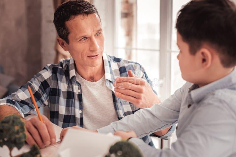 Ενθαρρύνετε τον πατέρα που βελτιώνει τις διαπροσωπικές σχέσεις του με το γιο του στοκ φωτογραφία με δικαίωμα ελεύθερης χρήσης