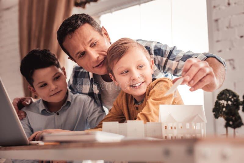 Ενθαρρύνετε τον πατέρα που λέει στους γιους του για τη ανανεώσιμη ενέργεια στοκ φωτογραφία