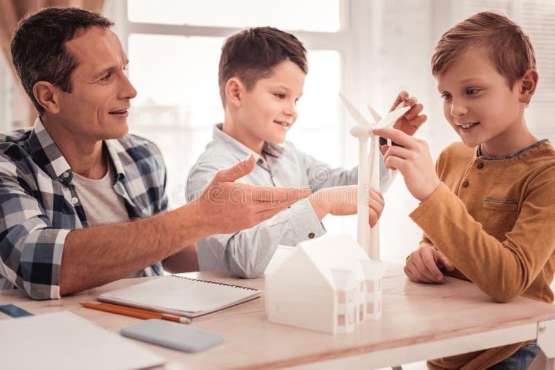 Ενθαρρύνετε τον πατέρα που φορά το τετραγωνικό πουκάμισο διδάσκοντας τα υιοθετημένα παιδιά του στοκ φωτογραφία
