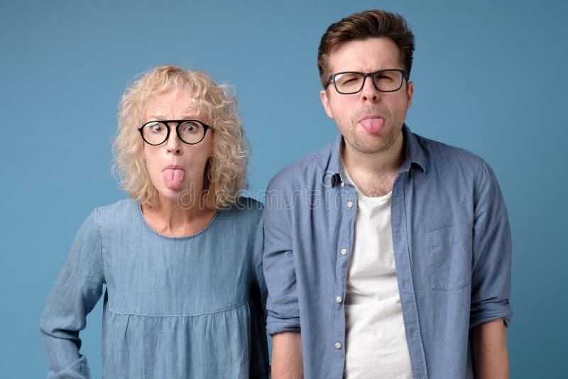 Ενθουσιασμένος αστείος κωμικός και χαρούμενος τύπος και γυναίκα που βγάζει γλώσσα έξω στοκ εικόνες με δικαίωμα ελεύθερης χρήσης