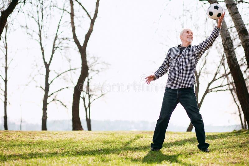 Ενθουσιώδες ώριμο άτομο που παίρνει τη σφαίρα στοκ εικόνα με δικαίωμα ελεύθερης χρήσης