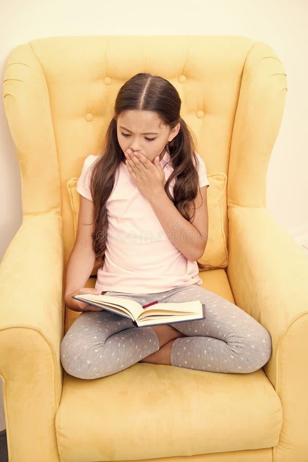 Ενθουσιώδης για τη διέγερση της ιστορίας Χόμπι ανάγνωσης Το παιδί κοριτσιών κάθεται το κίτρινο διαβασμένο πολυθρόνα βιβλίο Χαριτω στοκ εικόνα