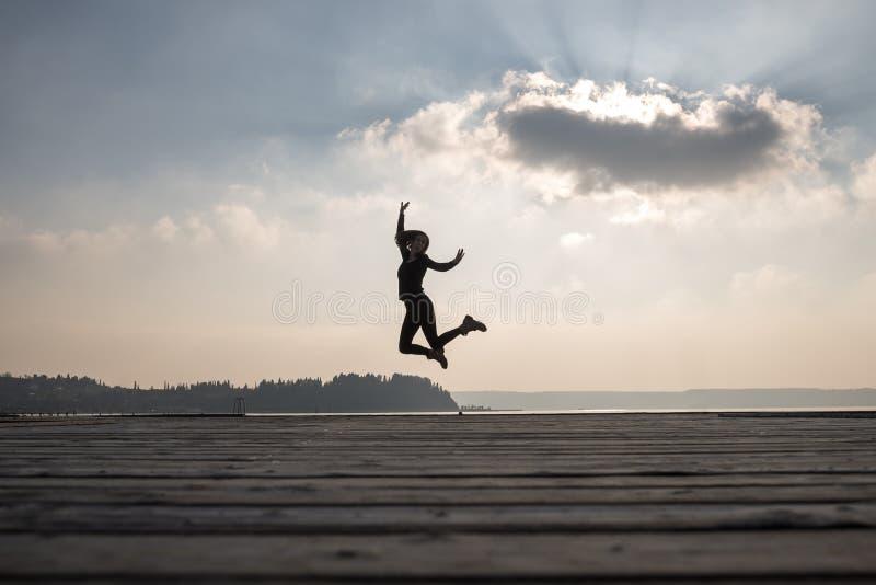 Ενθουσιώδης γυναίκα που πηδά στον αέρα ενάντια στον ουρανό στοκ εικόνες με δικαίωμα ελεύθερης χρήσης