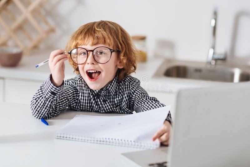 Ενθουσιώδες έξυπνο παιδί που εργάζεται στη γραφή του στοκ εικόνες με δικαίωμα ελεύθερης χρήσης