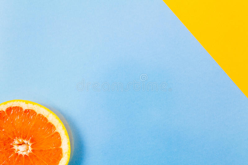 Ενιαία κινηματογράφηση σε πρώτο πλάνο φετών γκρέιπφρουτ στην μπλε και διαγώνια κίτρινη πλάτη στοκ εικόνες με δικαίωμα ελεύθερης χρήσης