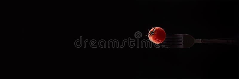 Ενιαία ντομάτα κερασιών σαλάτας στο δίκρανο που απομονώνεται στο μαύρο υπόβαθρο Έμβλημα 3:1 για τον Ιστό στοκ φωτογραφία με δικαίωμα ελεύθερης χρήσης