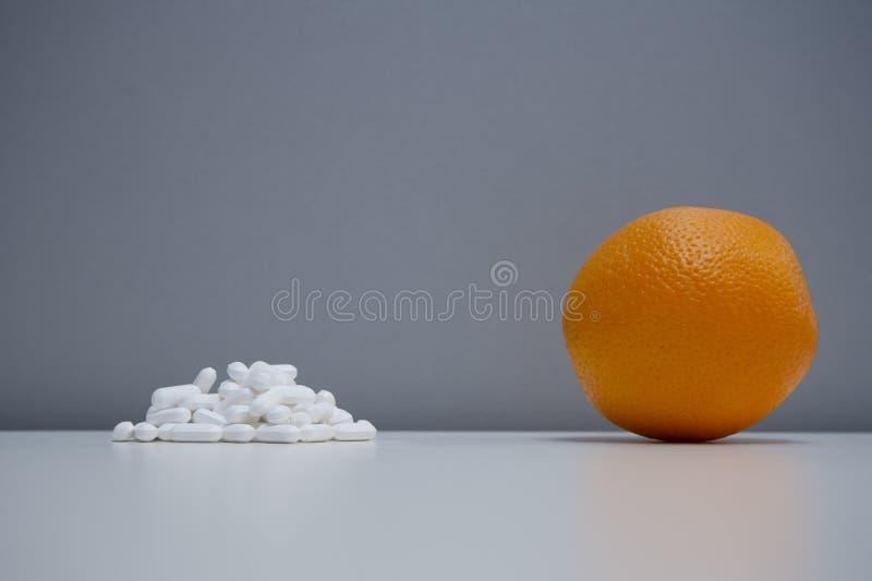 Ενιαία πορτοκαλιά φρούτα με το ιατρικό άσπρο χάπι στο υγιές γκρίζο υπόβαθρο έννοιας θεραπείας τροφίμων στοκ εικόνα με δικαίωμα ελεύθερης χρήσης