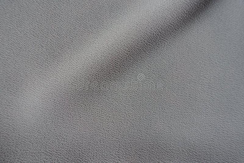 Ενιαίες διαγώνιες μαλακές πτυχές στο γκρίζο ύφασμα crepe-Georgette στοκ εικόνα