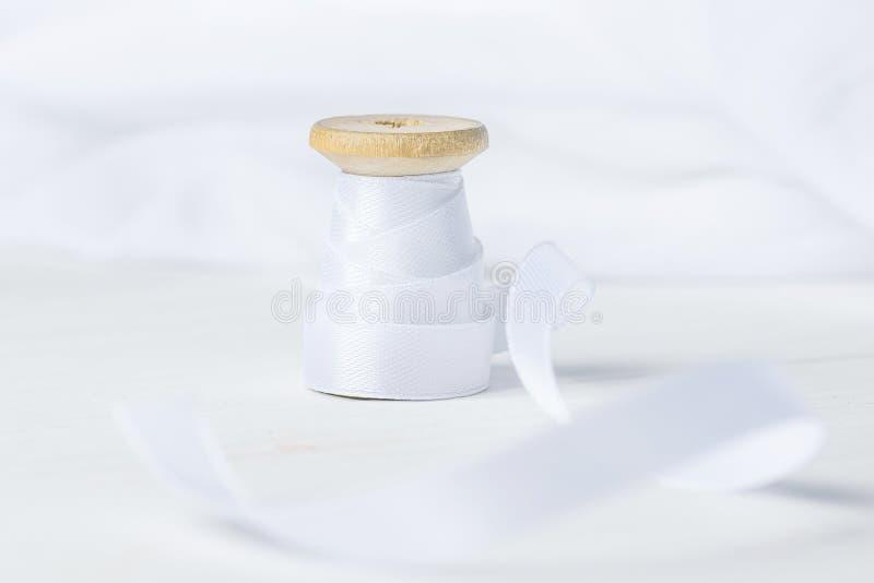 Ενιαίος ξύλινος ρόλος στροφίων με την κορδέλλα μεταξιού στο άσπρο υπόβαθρο υφάσματος λινού βαμβακιού Έννοια χόμπι τεχνών ραψίματο στοκ εικόνες