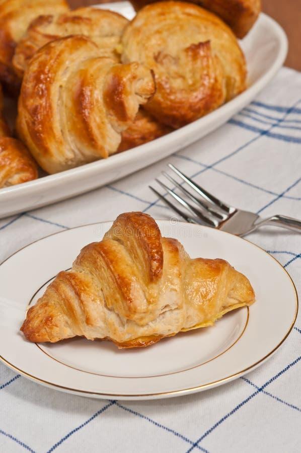 Ενιαίος πρόσφατα ψημένος, σπιτικός croissant σε ένα στρογγυλό, άσπρο πιάτο στοκ εικόνες