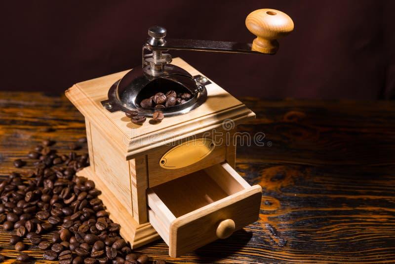 Ενιαίος χειρωνακτικός μύλος καφέ με τα διεσπαρμένα φασόλια στοκ φωτογραφία