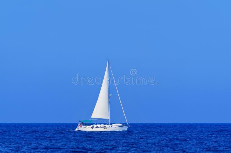 Ενιαίο άσπρο γιοτ στην ανοικτή θάλασσα ενάντια στο σαφή μπλε ουρανό στοκ φωτογραφία