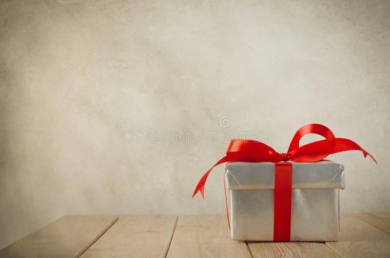 Ενιαίο ασημένιο κιβώτιο δώρων με το κόκκινο τόξο στοκ εικόνες με δικαίωμα ελεύθερης χρήσης