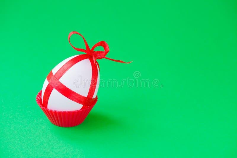 Ενιαίο αυγό Πάσχας με μια κόκκινη κορδέλλα στοκ φωτογραφίες