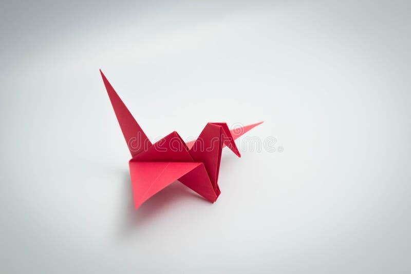 Ενιαίο κόκκινο origami πουλιών που απομονώνεται άσπρο σε στενό στοκ εικόνες