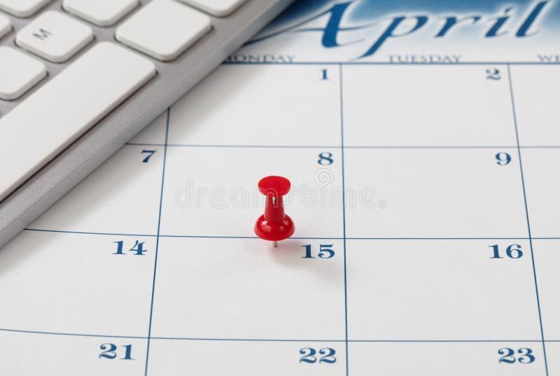 Ενιαίο κόκκινο pushpin στις 15 Απριλίου του ημερολογίου για την υπενθύμιση οφειλόμενης ημερομηνίας φορολογικών εσόδων στοκ φωτογραφίες