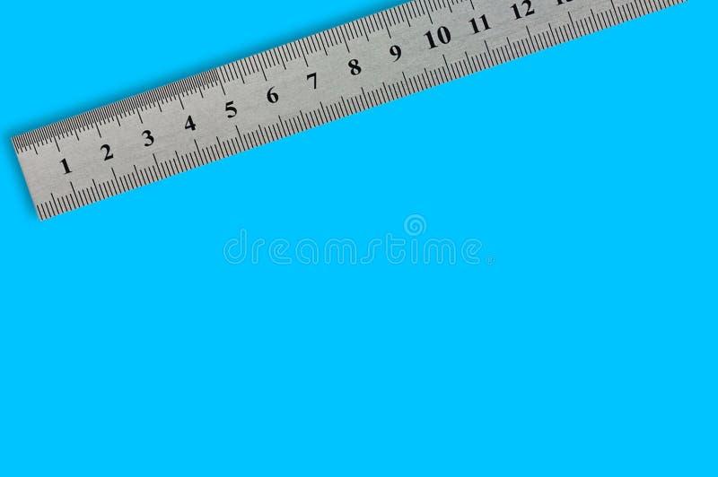 Ενιαίο μέταλλο straightedge με τα ψηφία και την κλίμακα στο μπλε υπόβαθρο στοκ εικόνα με δικαίωμα ελεύθερης χρήσης