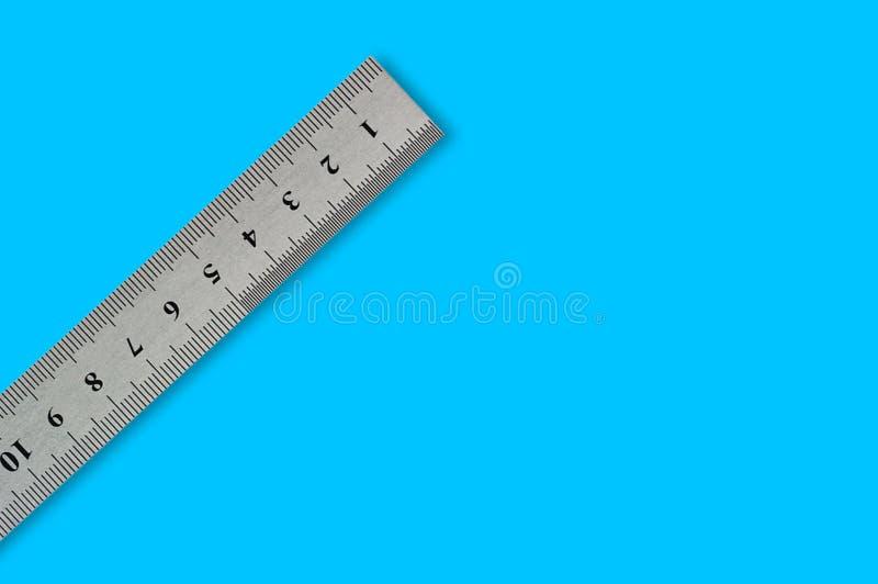 Ενιαίο μέταλλο straightedge με τα ψηφία και την κλίμακα στο μπλε υπόβαθρο στοκ φωτογραφία με δικαίωμα ελεύθερης χρήσης