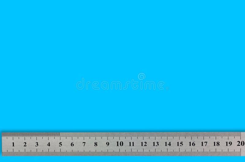 Ενιαίο μέταλλο straightedge με τα ψηφία και την κλίμακα στο μπλε υπόβαθρο στοκ εικόνες με δικαίωμα ελεύθερης χρήσης