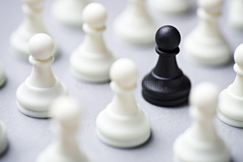 Ενιαίο μαύρο κομμάτι σκακιού μεταξύ άσπρων στοκ εικόνα