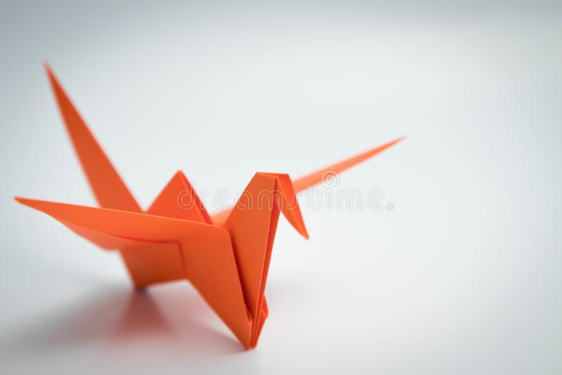 Ενιαίο πορτοκαλί origami πουλιών που απομονώνεται άσπρο σε στενό στοκ εικόνες με δικαίωμα ελεύθερης χρήσης