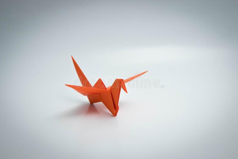 Ενιαίο πορτοκαλί origami πουλιών που απομονώνεται άσπρο σε στενό στοκ εικόνες