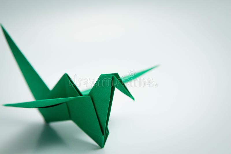 Ενιαίο πράσινο origami πουλιών που απομονώνεται άσπρο σε στενό στοκ φωτογραφία με δικαίωμα ελεύθερης χρήσης
