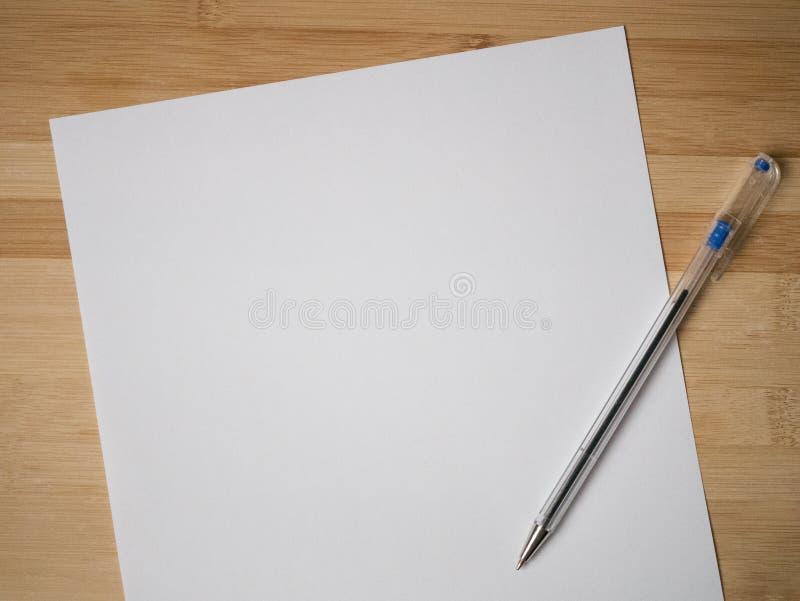 Ενιαίο φύλλο της κενής Λευκής Βίβλου με τη μάνδρα ballpoint στο ξύλο στοκ φωτογραφία με δικαίωμα ελεύθερης χρήσης