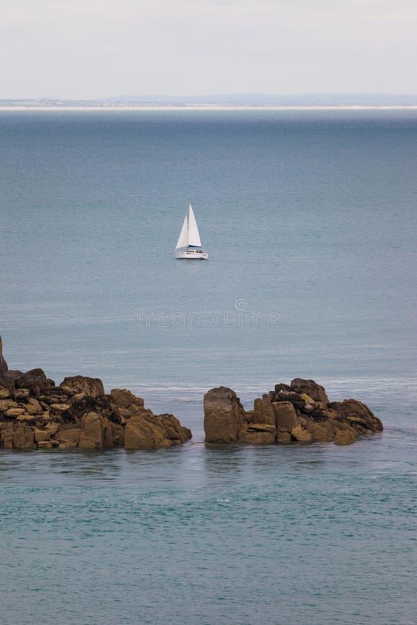 Ενιαίο saiboat πίσω από τους βράχους στοκ εικόνες