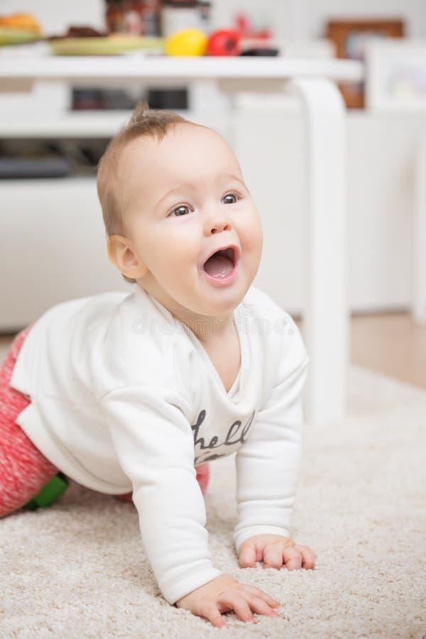 Εννέα μηνών παιχνιδιού κοριτσάκι που σέρνεται στο πάτωμα στοκ φωτογραφίες