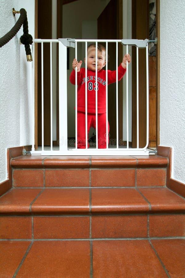 Εννέα μηνών παλαιό αρσενικό μωρών πίσω από το κλουβί στοκ φωτογραφίες
