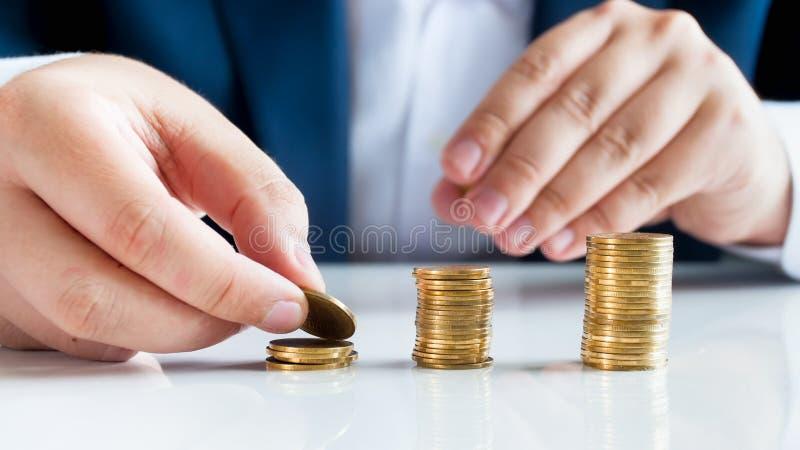 Εννοιολογική εικόνα της οικονομικής και σταθερότητας τραπεζών, επιχειρηματίας που βάζει τα νομίσματα στους υψηλούς σωρούς στοκ εικόνες με δικαίωμα ελεύθερης χρήσης