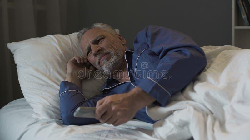 Ενοχλημένος συνταξιούχος που υφίσταται την αϋπνία και νευρικά που αλλάζει τα τηλεοπτικά κανάλια στοκ εικόνες με δικαίωμα ελεύθερης χρήσης