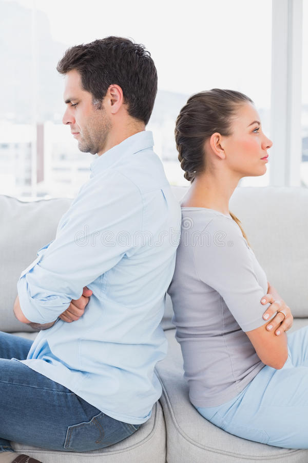 Ενοχλημένη συνεδρίαση ζευγών πλάτη με πλάτη στον καναπέ στοκ φωτογραφίες