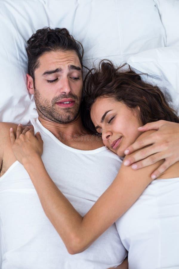 Ενοχλημένος άνδρας που εξετάζει τη χαλάρωση γυναικών στο κρεβάτι στοκ φωτογραφία