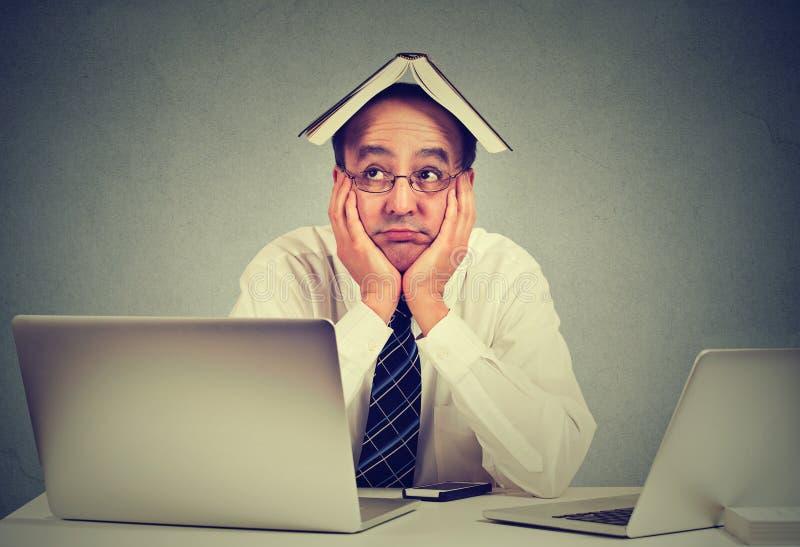 Ενοχλημένος, τρυπημένος, κούρασε, άτομο, αστείος δάσκαλος με το βιβλίο στο κεφάλι, που κάθεται στο γραφείο, που ταΐστηκε επάνω τη στοκ εικόνες με δικαίωμα ελεύθερης χρήσης
