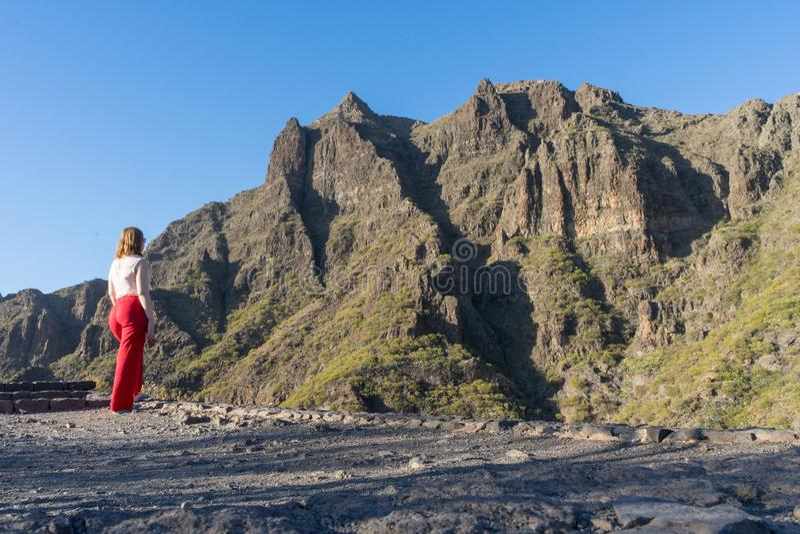 Εντυπωσιακός καυκάσιος τουρίστας με κόκκινα παντελόνια σε τοπία κρυμμένο, στέκεται με ηρεμία και χαλαρώνει Αρμονική γυναίκα στοκ εικόνα