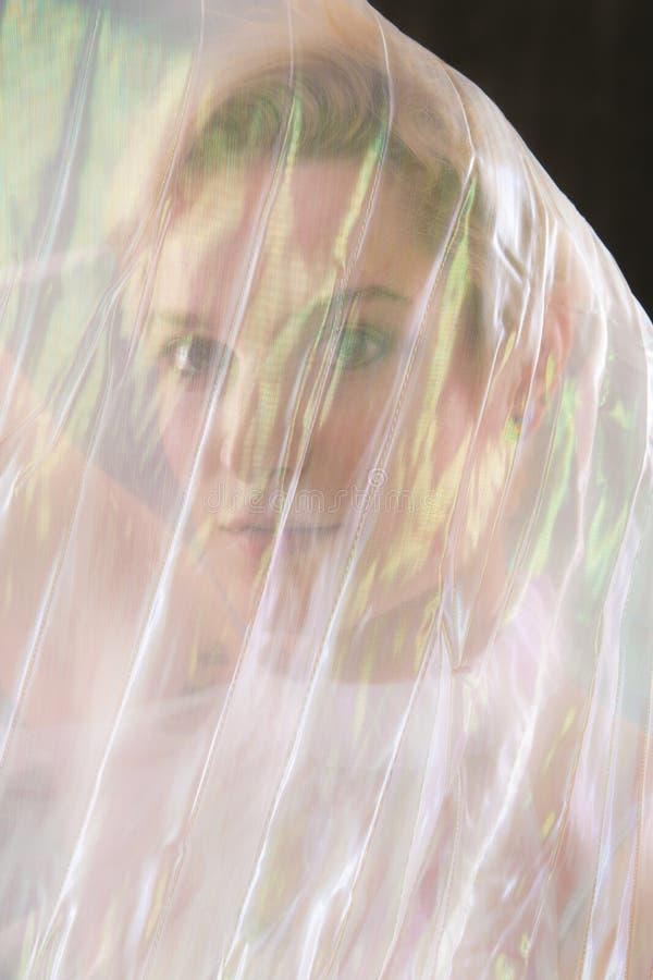 Εντυπωσιακό πορτρέτο της νέας γυναίκας που τυλίγεται gossamer στο ακρωτήριο στοκ φωτογραφία