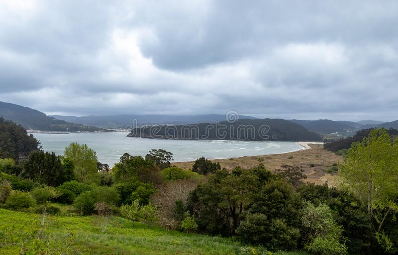 Εντυπωσιακό τοπίο μιας παραλίας που περιβάλλεται από το δάσος με τα διαφορετικά και ζωηρόχρωμα δέντρα σε ένα Coruña, Γαλικία, Ισ στοκ εικόνες